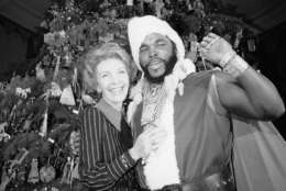 First lady Nancy Reagan enlists the help of television's Mr. T during a Christmas tour of the White House for the media on Monday, Dec. 13, 1983 in Washington. The two are shown in front of the executive mansion's official Christmas tree, a 20-foot Noble fir containing about 2,000 ornaments and several thousand lights, in the Blue Room. (AP Photo/Ira Schwarz)
