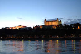 ** FILE ** The Bratislava castle is illuminated above river Danube in this May 8, 2005 file photo. The house of Slovak parliament can be seen at left. (AP Photo/Jan Koller, CTK)