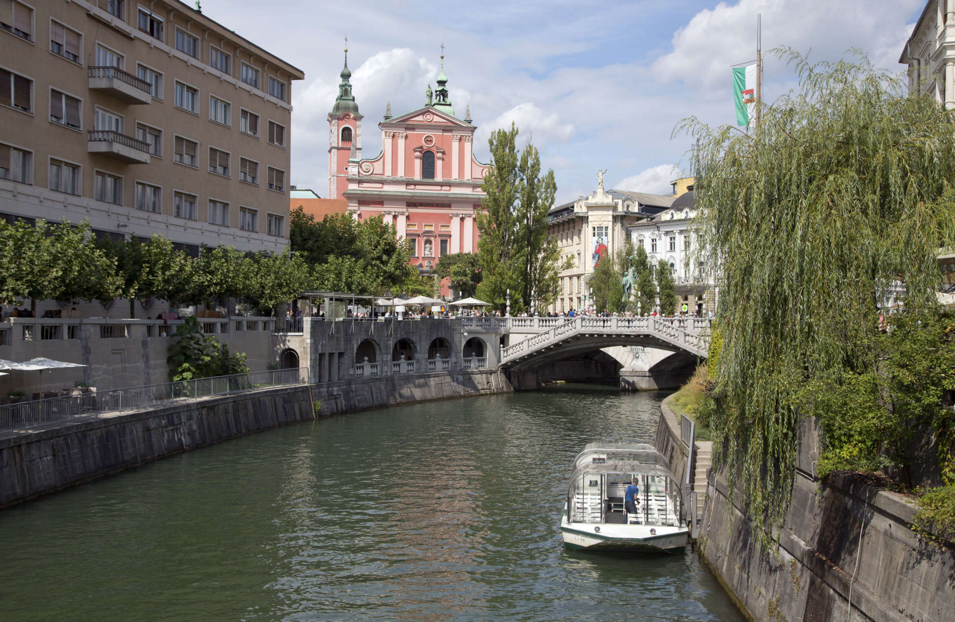 FILE - In this Aug. 12, 2016 file photo, tourists and residents walk across Tromostovje bridge in downtown Ljubljana, Slovenia. The tiny European nation of Slovenia is getting an outsize share of attention lately. Not only has Melania Trump, wife of U.S. President-elect Donald Trump. given her native country a boost of recognition, but Slovenia's also in the midst of a tourism boom. (AP Photo/Darko Bandic, File)