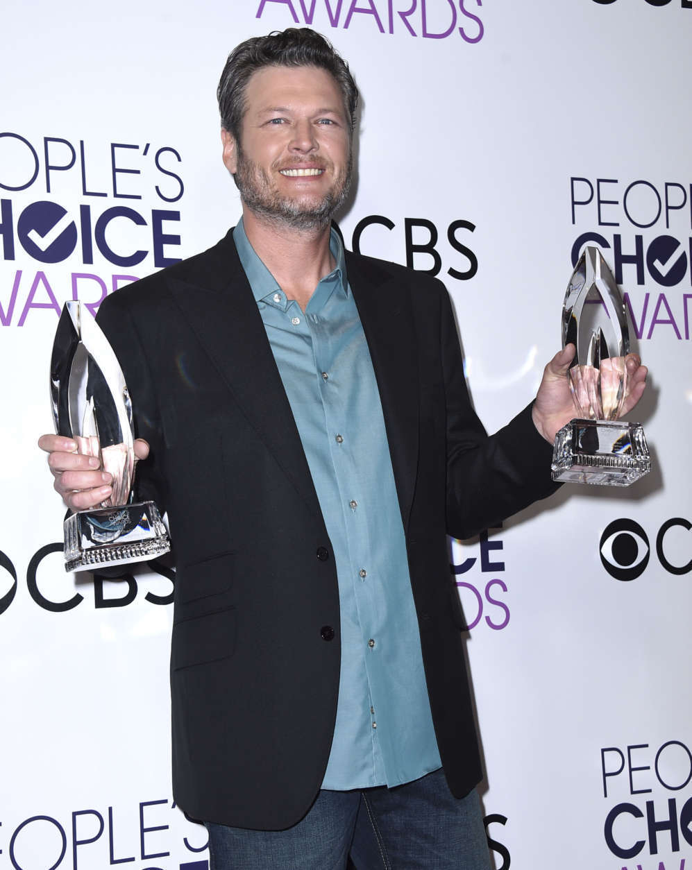 "Blake Shelton poses in the press room with the awards for favorite album for ""If I'm Honest"" and favorite country male artist at the People's Choice Awards at the Microsoft Theater on Wednesday, Jan. 18, 2017, in Los Angeles. (Photo by Jordan Strauss/Invision/AP)"