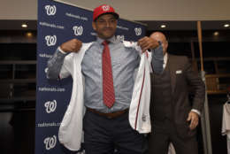 Washington Nationals new manager Dave Martinez puts on a jersey during a baseball press conference, Thursday, Nov. 2, 2017, in Washington. At right is general manager Mike Rizzo. (AP Photo/Nick Wass)