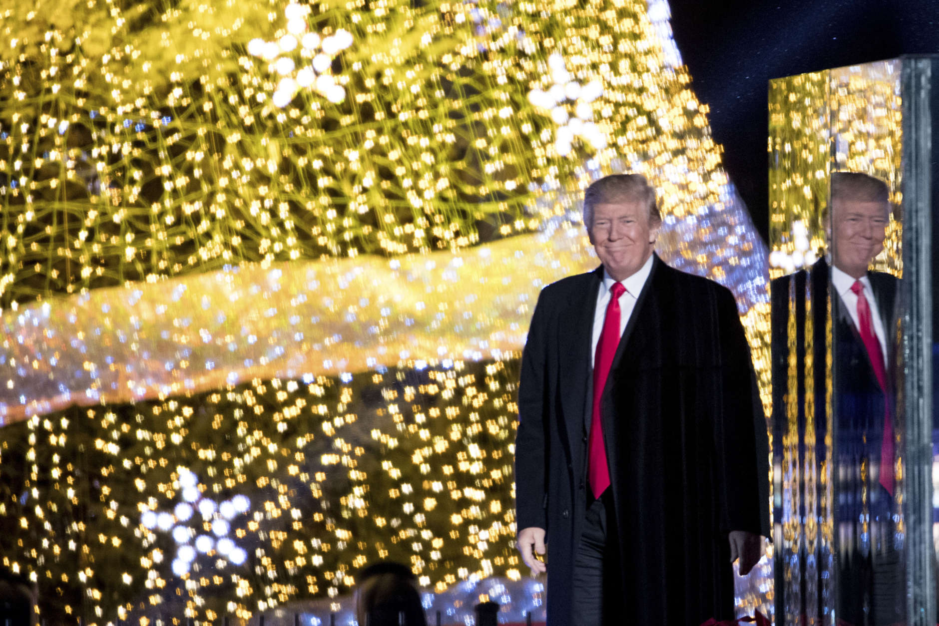 President Donald Trump stands on stage after lighting the 2017 National Christmas Tree on the Ellipse near the White House, Thursday, Nov. 30, 2017, in Washington. (AP Photo/Andrew Harnik)