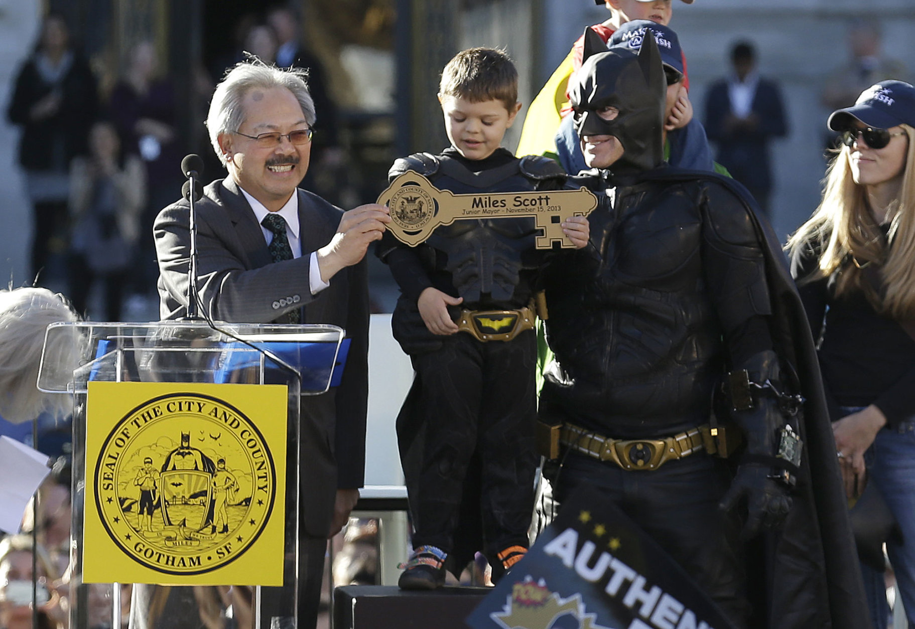 FILE - In this Nov. 15, 2013 file photo, Miles Scott, dressed as Batkid, stands next to Batman as he receives the key to the city from San Francisco Mayor Ed Lee, left, at a rally outside of City Hall in San Francisco. Mayor Lee, who oversaw a technology-driven economic boom in San Francisco that brought with it sky-high housing prices despite his lifelong commitment to economic equality, died suddenly early Tuesday, Dec. 12, 2017, at age 65. (AP Photo/Jeff Chiu, File)