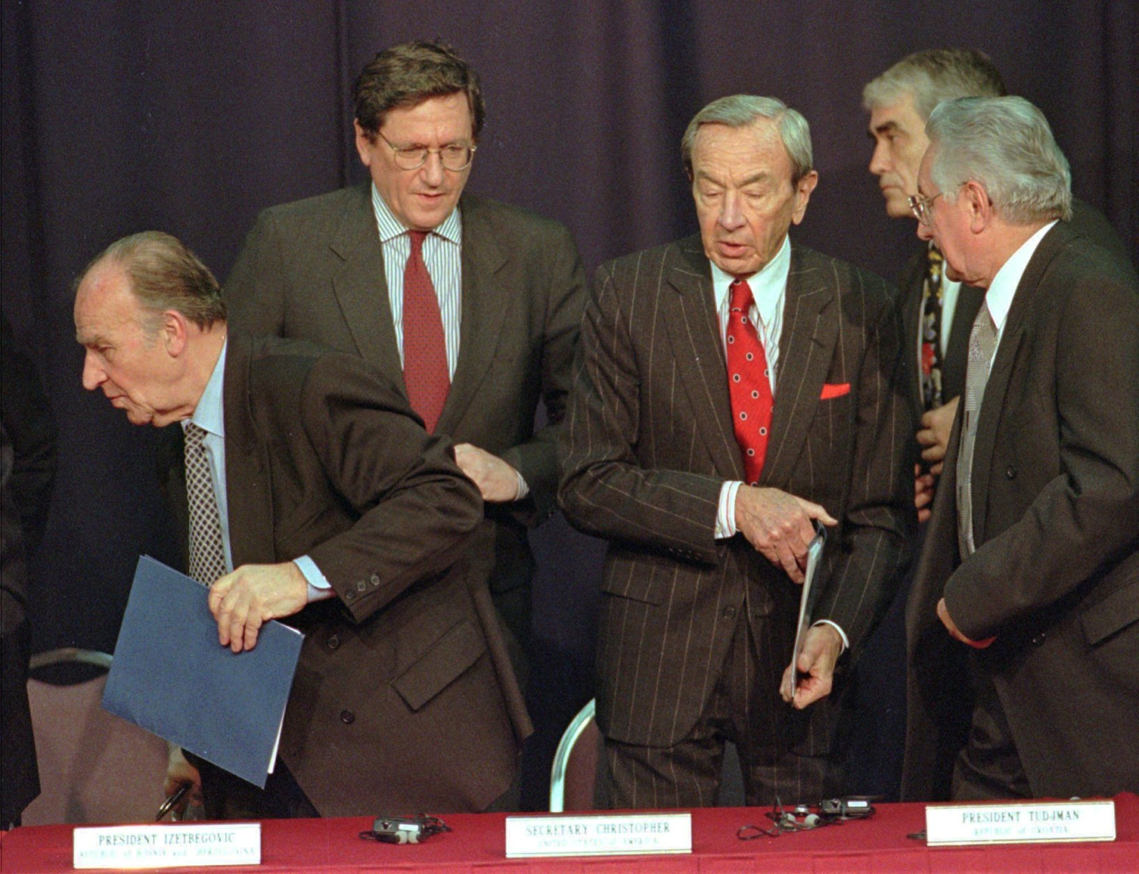 Secretary of State Warren Christopher, right center, steps between Bosnia President Alija Izetbegovic, left, and Croatian President Franjo Tudjman after they signed an accord Friday, Nov. 10, 1995, at Wright-Patterson Air Force Base in Dayton, Ohio, that bolsters a Muslim-Croat alliance that is seen as a fundamental building block for a Bosnia peace agreement. At left rear is U.S. negotiator Richard Holbrooke. (AP Photo/Al Behrman)