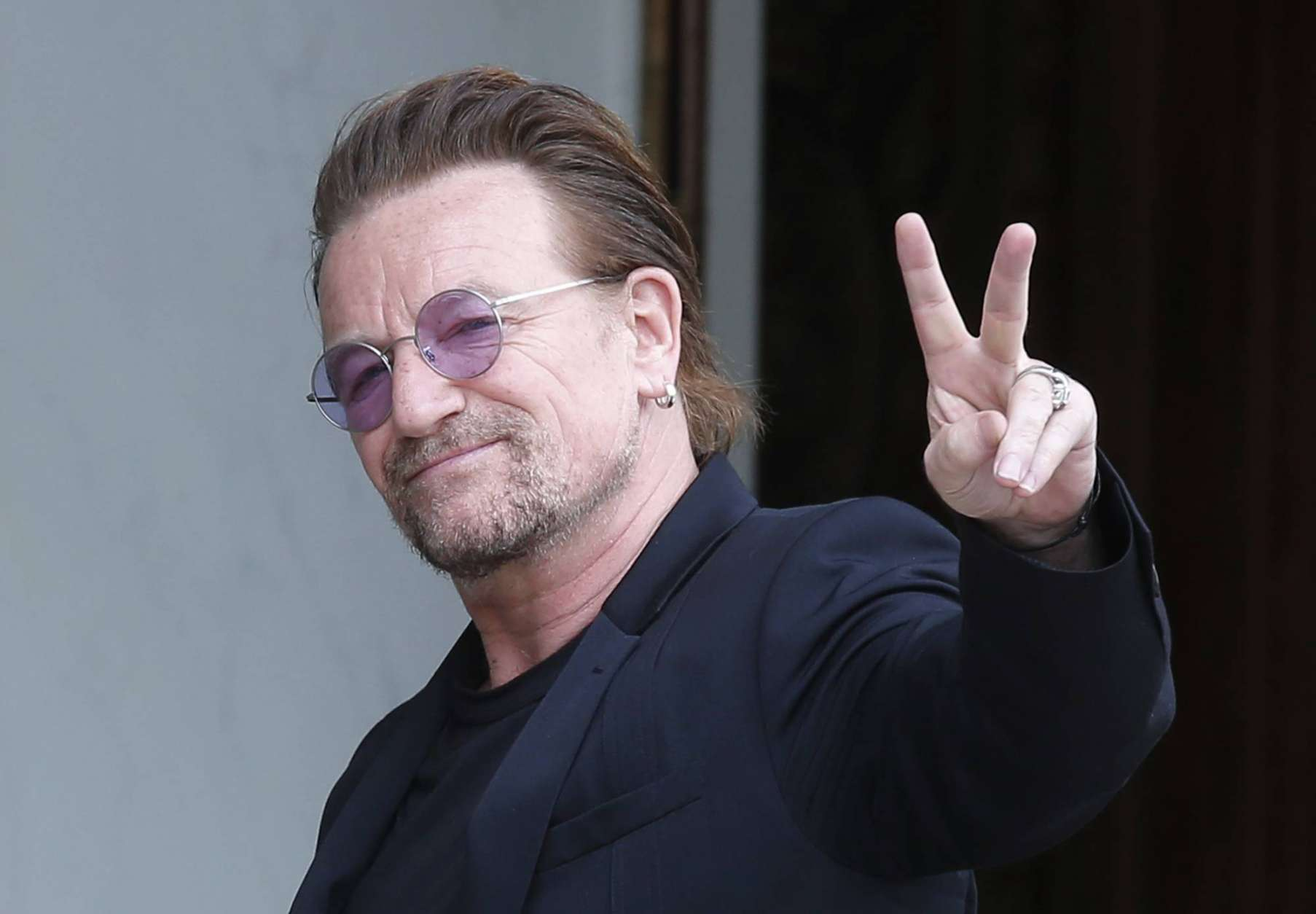 FILE - In this July 24, 2017, file photo, U2 singer Bono makes a peace sign as he arrives for a meeting at the Elysee Palace, in Paris, France. Bono will break a longstanding promise among the band not to play golf in order to raise money for his (RED) charity in the fight against HIV/AIDS. The chance to play mini-golf with U2 is just one of the celebrity experiences that are being raffled off as part of the (RED) Shopathon campaign for World AIDS Day on Dec. 1 at Omaze.com/RED. (AP Photo/Michel Euler, File)