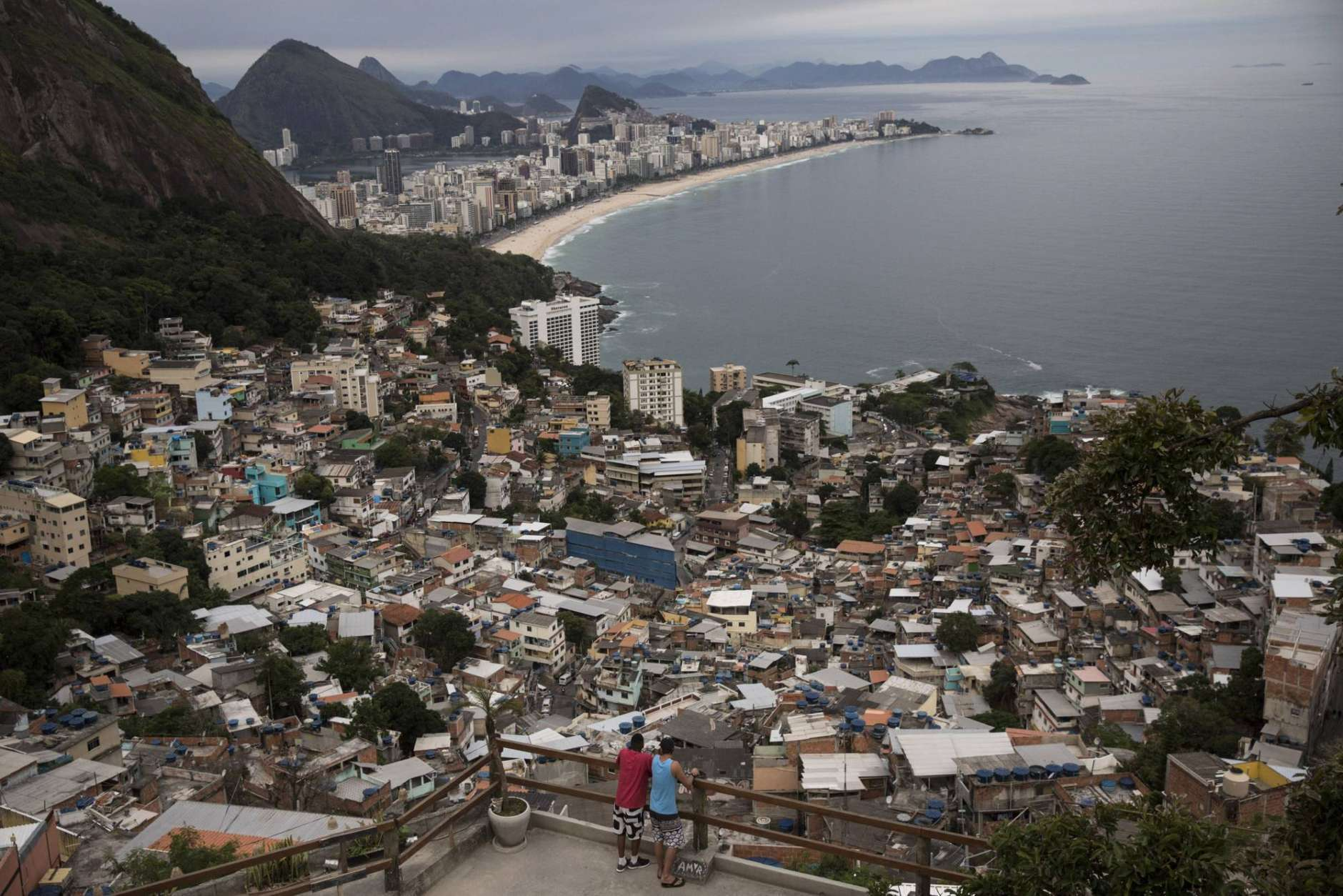 In this Oct. 29, 2017 photo, men overlook the city from the Vidigal slum, in Rio de Janeiro, Brazil. Opening the hillside favelas to tourists seemed like a winning idea: they get breathtaking views, the slum residents could cash in, and foreign visitors would see another part of the city, but soaring violence has rekindled a concern about safety. (AP Photo/Renata Brito)