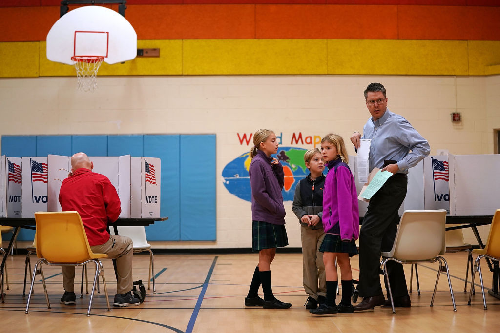 FILE — Children accompany their father as he votes at the polling place in the gymnasium at Washington Mill Elementary School on Nov. 7, 2017 in Alexandria, Virginia. (Photo by Chip Somodevilla/Getty Images)
