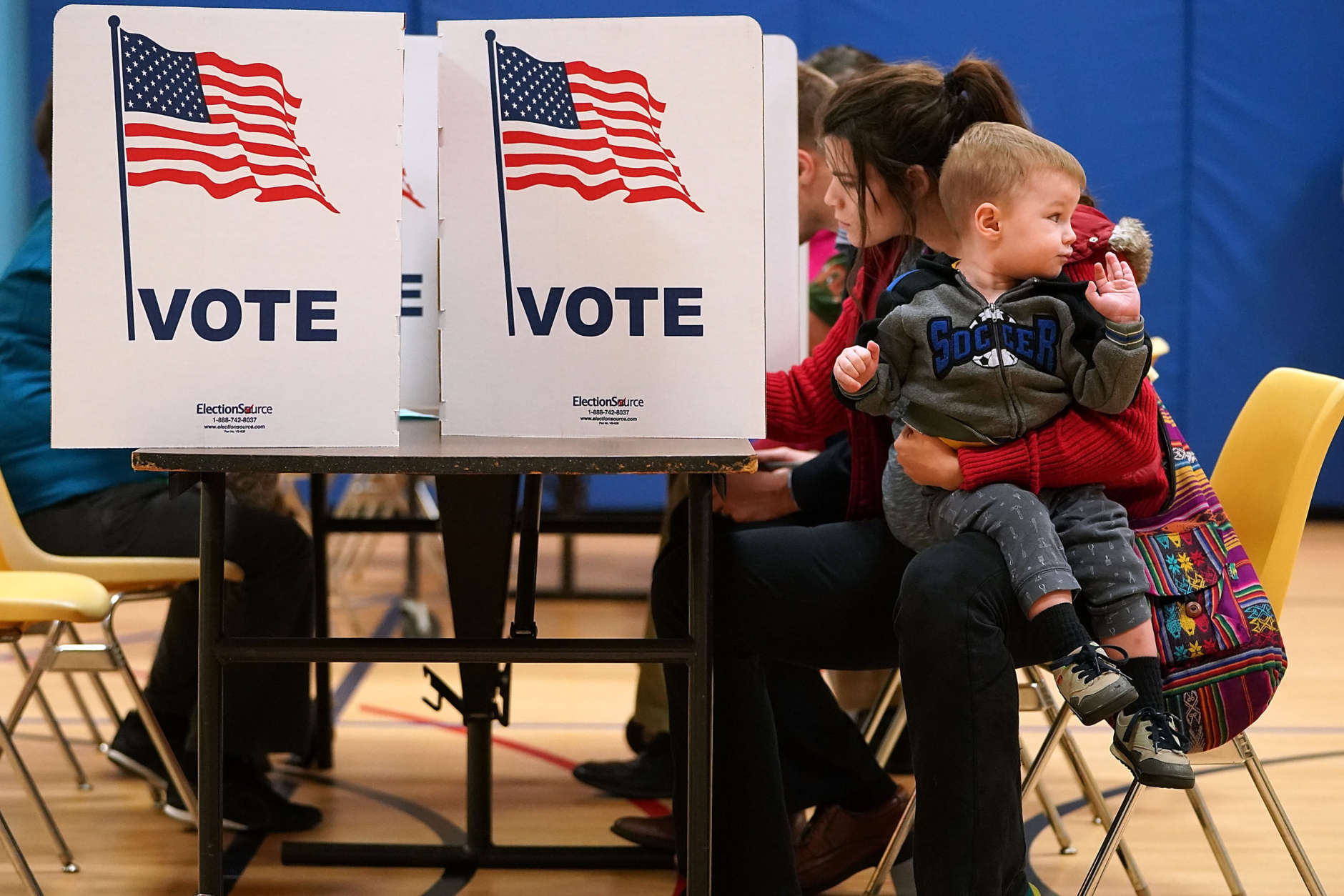 ALEXANDRIA, VA - NOVEMBER 07:   Karina Smith holds her 2-year-old son Kyler as she fills out her ballot at the polling place at Washington Mill Elementary School November 7, 2017 in Alexandria, Virginia. (Photo by Chip Somodevilla/Getty Images)