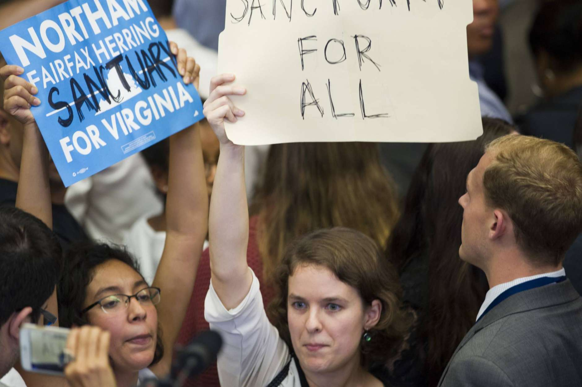 Protestors interrupt Virginia Gov. elect Ralph Northam as he addresses supporters at the Northam For Governor election night party at George Mason University in Fairfax, Va., Tuesday, Nov. 7, 2017. (AP Photo/Cliff Owen)