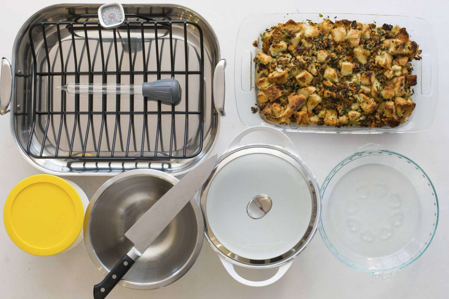 This Oct. 16, 2017 photo provided by Katie Workman shows some must have Thanksgiving tools in New York. Pictured are a roasting oasting pan with rack, baster, instant thermometer, glass baking dish, glass pie plate, casserole pot, mixing bowl, chef's knife and storage containers. (Sarah Crowder/Katie Workman via AP)