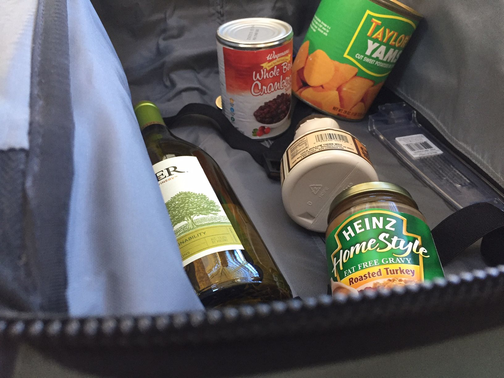 """The TSA's Lisa Farbstein says, """"If you can spill it, spray it, spread it, pump it or pour it, it's considered a liquid, gel or aerosol, and that should go in your checked bag if it's larger than 3.4 ounces."""" That includes cans -- so all these sauces and gravies need to be in a checked bag. (WTOP/Dennis Foley)"""
