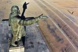 "FILE - In this aerial file photo taken on Tuesday, Oct. 31, 2017, a woman walks past a statue of Soviet Union founder Vladimir Lenin at the Russian leased Baikonur cosmodrome, in Kazakhstan. The thousands of statues of Vladimir Lenin spread across the vast region bring to mind poet Vladimir Mayakovsky's ringing line of devotion: ""Lenin lived, Lenin lives, Lenin will live."" (AP Photo/Dmitry Lovetsky, file)"