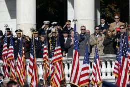 People salute or place their hands over their hearts during the playing of the national anthem during a Veterans Day ceremony at Arlington National Cemetery, Saturday, Nov. 11, 2017, in Washington. (AP Photo/Alex Brandon)