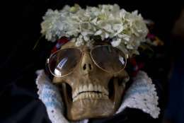 A human skull wearing sun glasses and flowers is displayed outside the General Cemetery chapel during the Natitas Festival in La Paz, Bolivia, Wednesday, Nov. 8, 2017. Every year, hundreds of Bolivians carry human skulls adorned with flowers to a cemetery in La Paz, asking for fortune, health, and other favors as part of the celebration. (AP Photo/Juan Karita)
