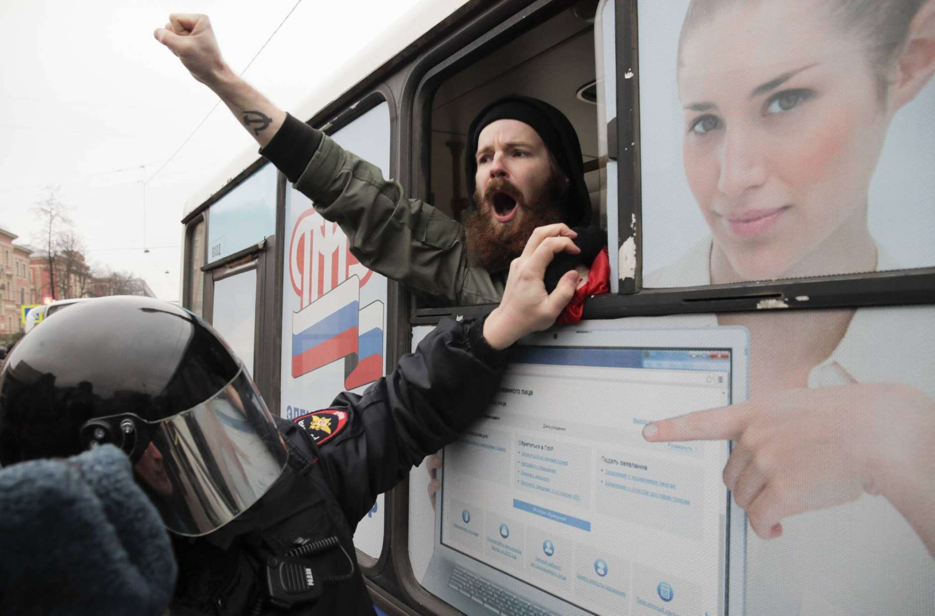 A detained member of the Other Russia movement shouts from a police bus during an unauthorized rally to mark the centenary of the Bolshevik Revolution in St. Petersburg, Russia, on Monday, Nov. 6, 2017. The Kremlin is avoiding any official commemoration of the anniversary, tip-toeing around the event that remains polarizing for many. (AP Photo/Dmitri Lovetsky)