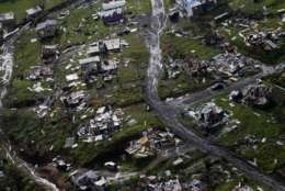 "FILE - In this Sept. 28, 2017, file photo, debris scatters a destroyed community in the aftermath of Hurricane Maria in Toa Alta, Puerto Rico. Still recovering from Hurricane Maria, Puerto Rico is getting a helping hand from an unlikely source, Moe from ""The Simpsons."" The bartender from the animated comedy in a new YouTube video is seen fundraising after getting a warm message by San Juan mayor Carmen Yulin Cruz. (AP Photo/Gerald Herbert, File)"