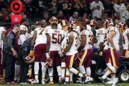 Teammates crowd around Washington Redskins running back Chris Thompson as he is helped onto a cart after being injured in the second half of an NFL football game against the New Orleans Saints in New Orleans, Sunday, Nov. 19, 2017. (AP Photo/Butch Dill)