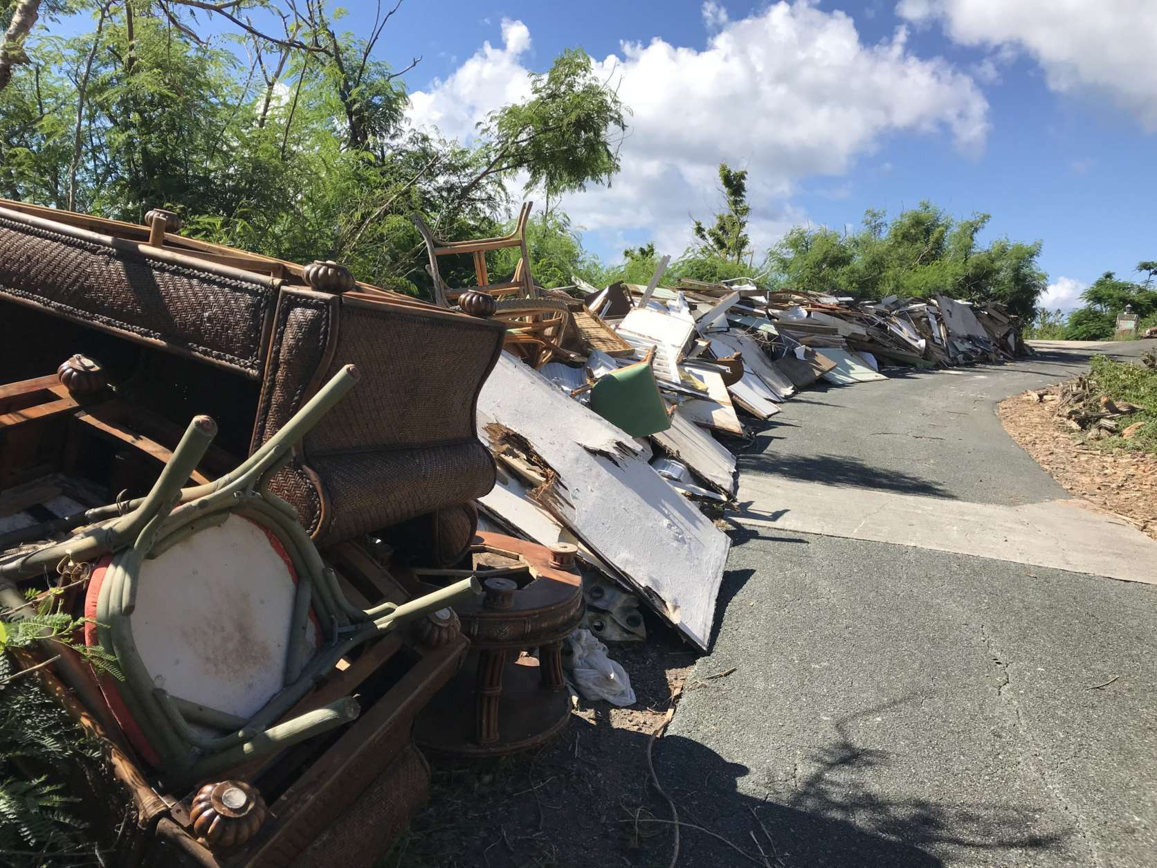 Debris neatly lines the streets in Great Cruz Bay for blocks on end. (WTOP/Jeff Clabaugh)