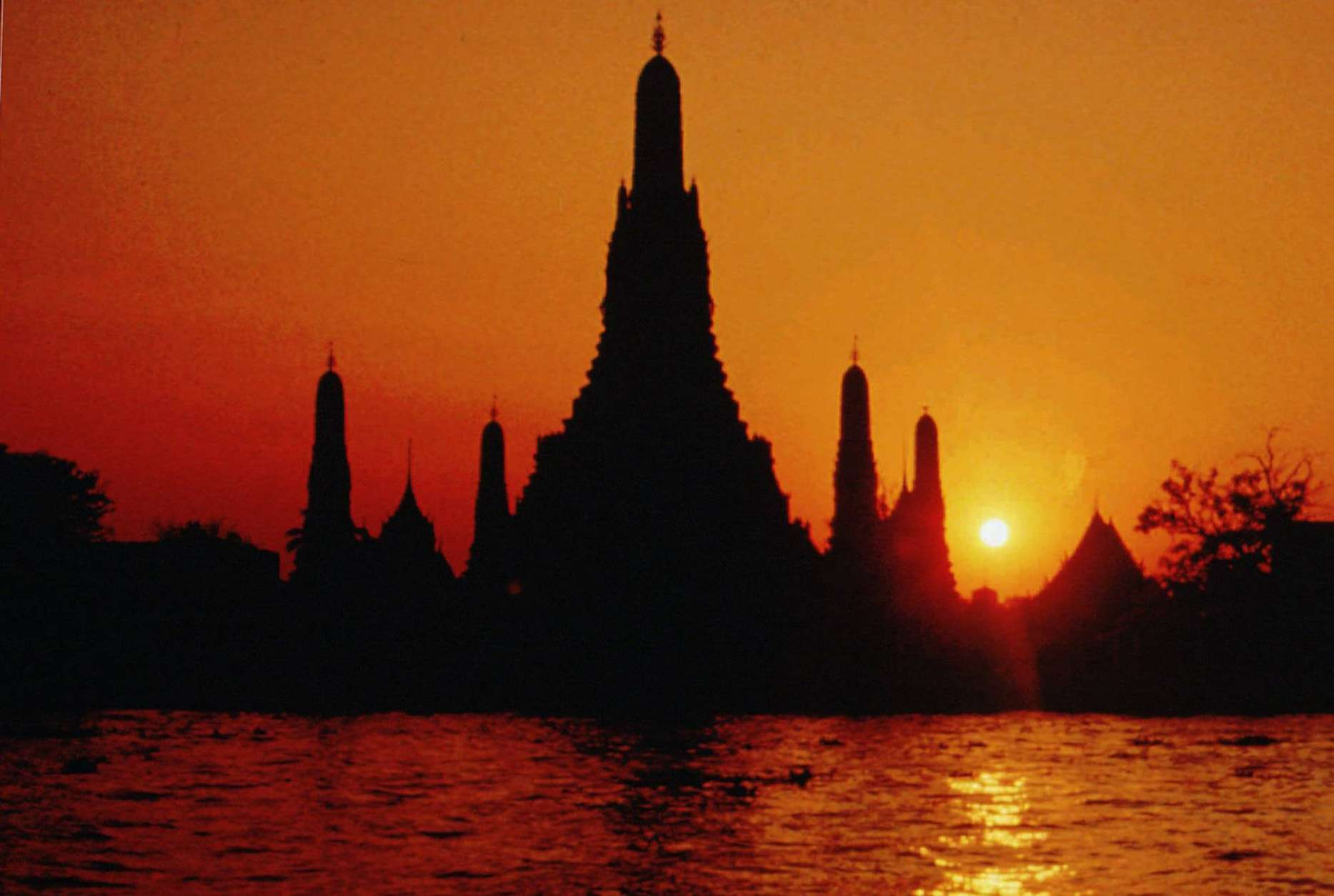 "FILE - In this April, 1996, file photo, the sun sets behind the stupa of the Buddhist temple Wat Arun or the ""Temple of Dawn"" seen from across the banks of the Chao Phraya river in Bangkok, Thailand. Two Americans who maintained a social media account called ""Traveling Butts"" have been arrested in Thailand after posting photos of themselves at the famous temple with their rear ends exposed. Deputy police spokesman Krisana Pattanacharoen says the men were arrested Tuesday night at a Bangkok airport and face public indecency charges. (AP Photo/Sakchai Lalit, File)"