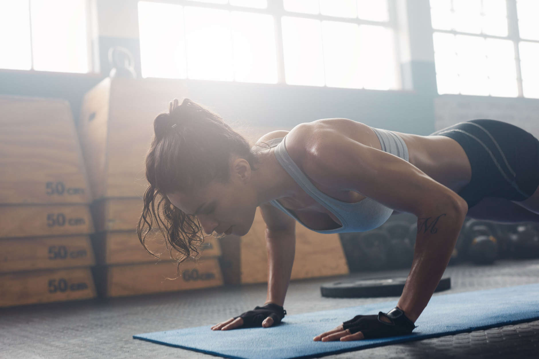 Shot of young woman doing push-ups at the gym. Muscular female doing pushups on exercise mat at gym. Female exercising on fitness mat at gym. (Thinkstock)