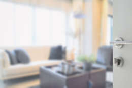 opened white door to modern living room interior