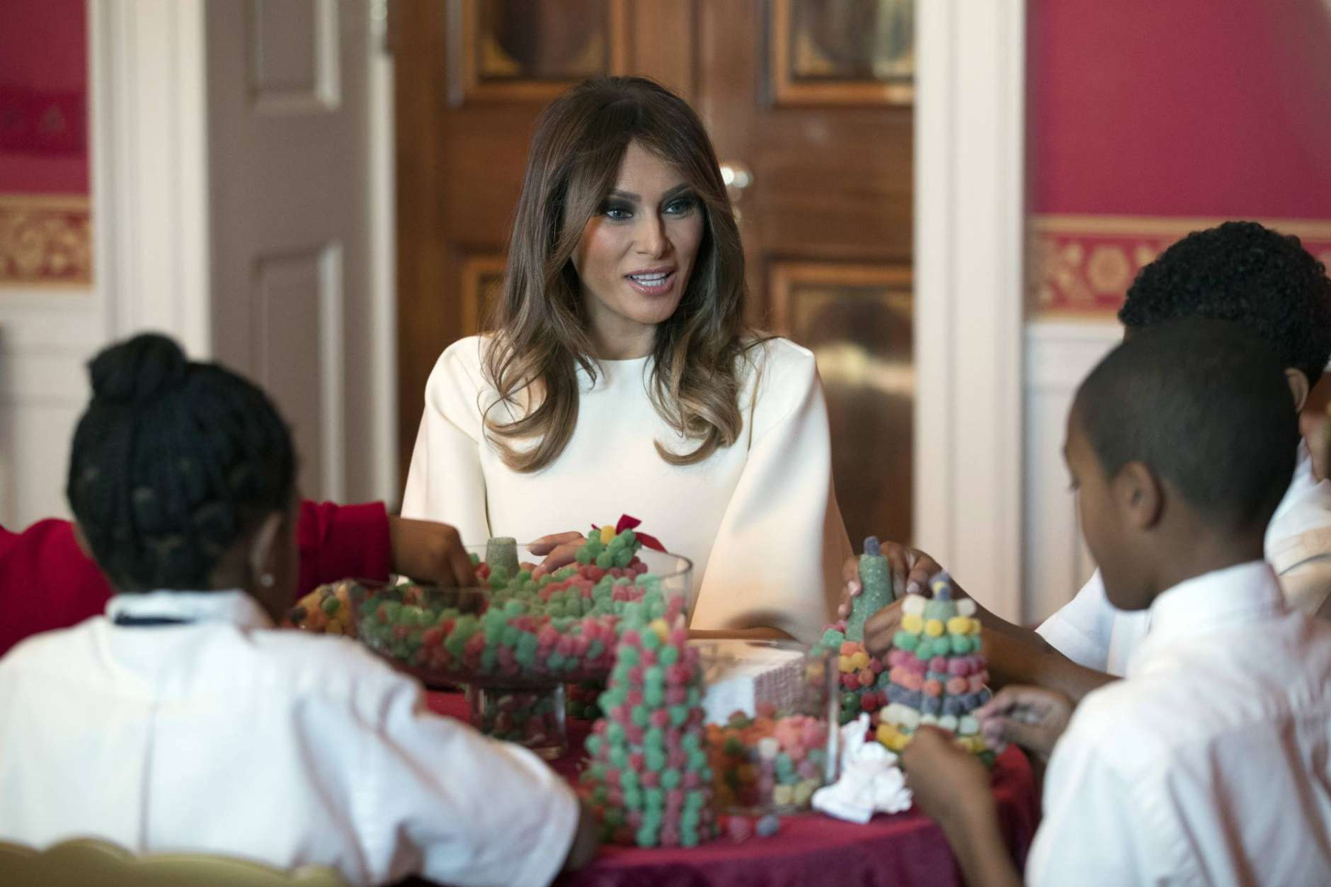 "First lady Melania Trump visits with children in the Red Room working on holiday treats among the 2017 holiday decorations with the theme ""Time-Honored Traditions"" at the White House in Washington, Monday, Nov. 27, 2017. The First Lady honored 200 years of holiday traditions at the White House. (AP Photo/Carolyn Kaster)"