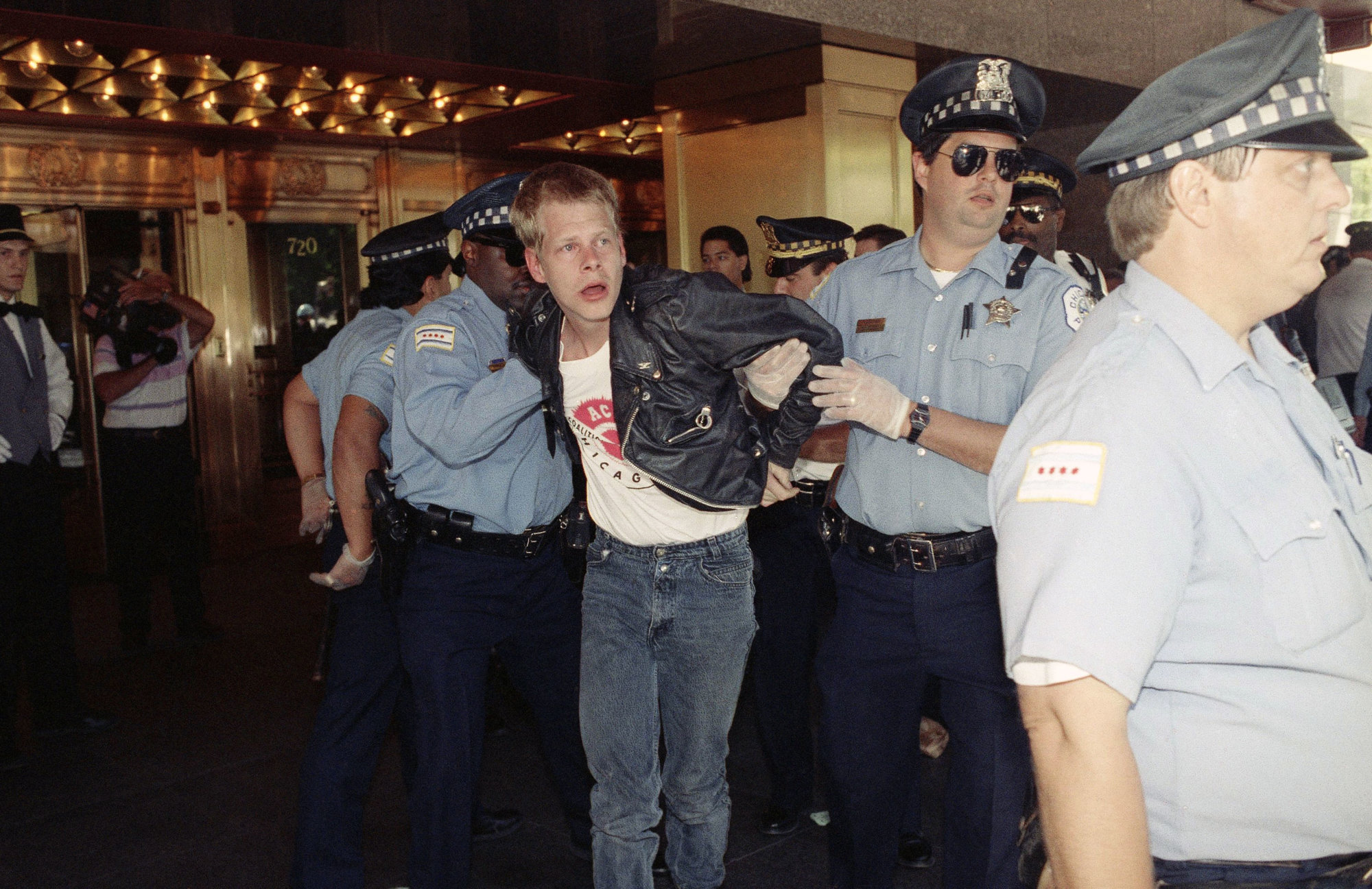 Chicago police officers, wearing rubber gloves, arrest a demonstrator outside the downtown hotel where the American Medical Association is holding its annual meeting in Chicago, June 24, 1991. Members of the AIDS Coalition to Unleash Power (ACT-UP) are protesting the AMA's AIDS policies. (AP Photo/John Swart)