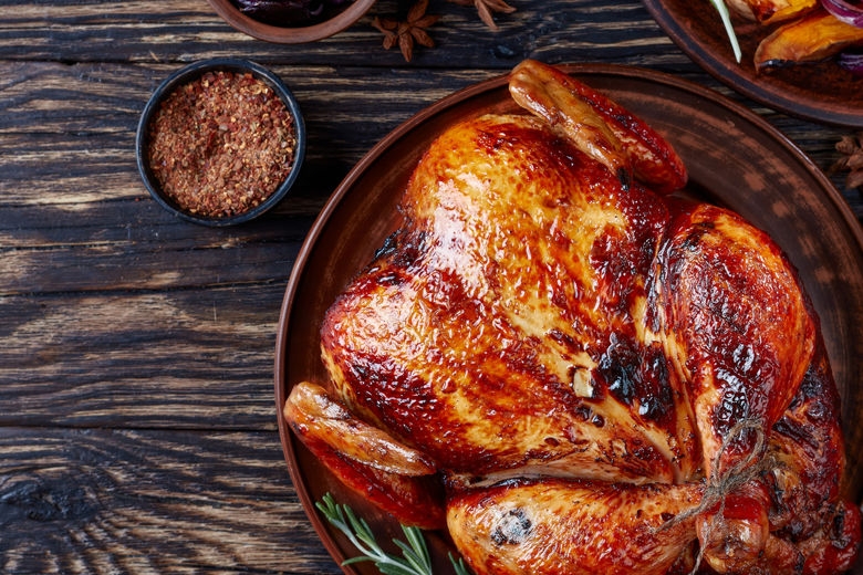 whole roasted chicken with golden brown crispy skin served on a earthenware dish with caramelized grilled pumpkin slices and grilled onion, view from above, flat lay, copy space