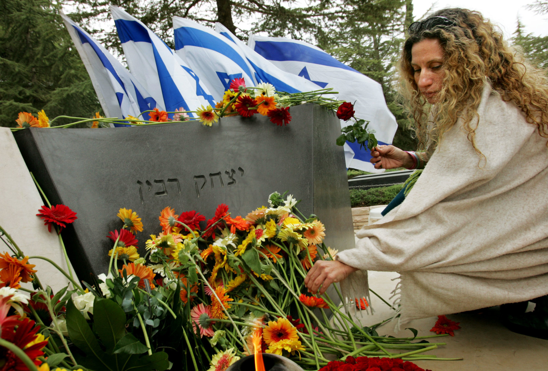 An Israeli woman lays a flower at the grave of late Israeli Prime Minister Yitzhak Rabin during a memorial at Mount Hertzl cemetery in Jerusalem, Friday, Nov. 4, 2005. On the 10-year anniversary of the assassination of Prime Minister Yitzhak Rabin, the official who was responsible for the Israeli leader's security is calling for a new investigation into the killing. (AP Photo/Kevin Frayer)