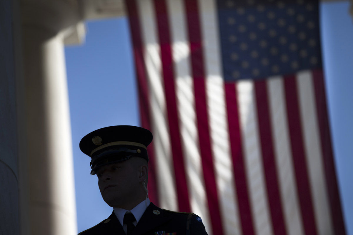 A member of the honor guard waits for the arrival of visitors to the annual Veterans Day Observance Ceremony at Arlington National Cemetery in Arlington, Va., Tuesday, Nov. 11, 2014. Americans marked Veterans Day on Tuesday with parades, speeches and military discounts, while in Europe the holiday known as Armistice Day held special meaning in the centennial year of the start of World War I.   (AP Photo/Evan Vucci)