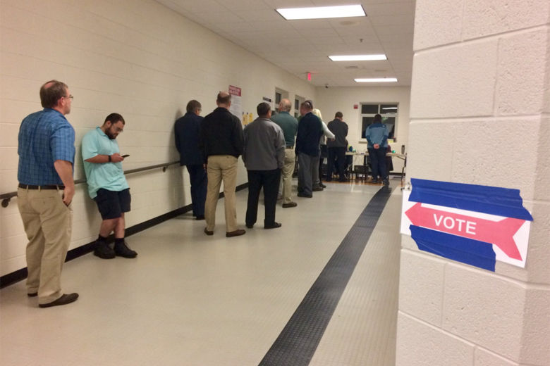 Picture shows people in line to vote