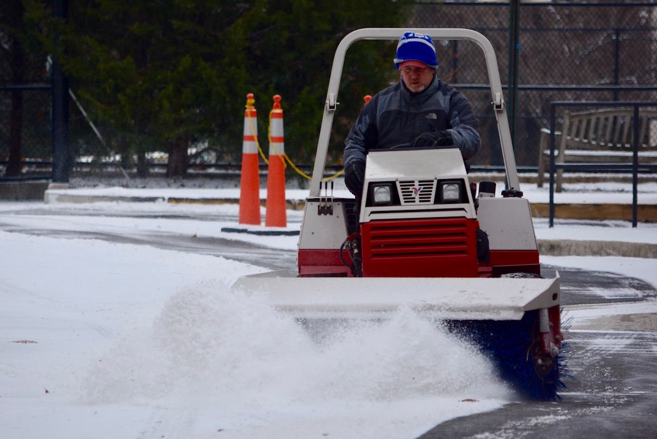 A power brusher pushes away snow Saturday morning. (WTOP/Dave Dildine)