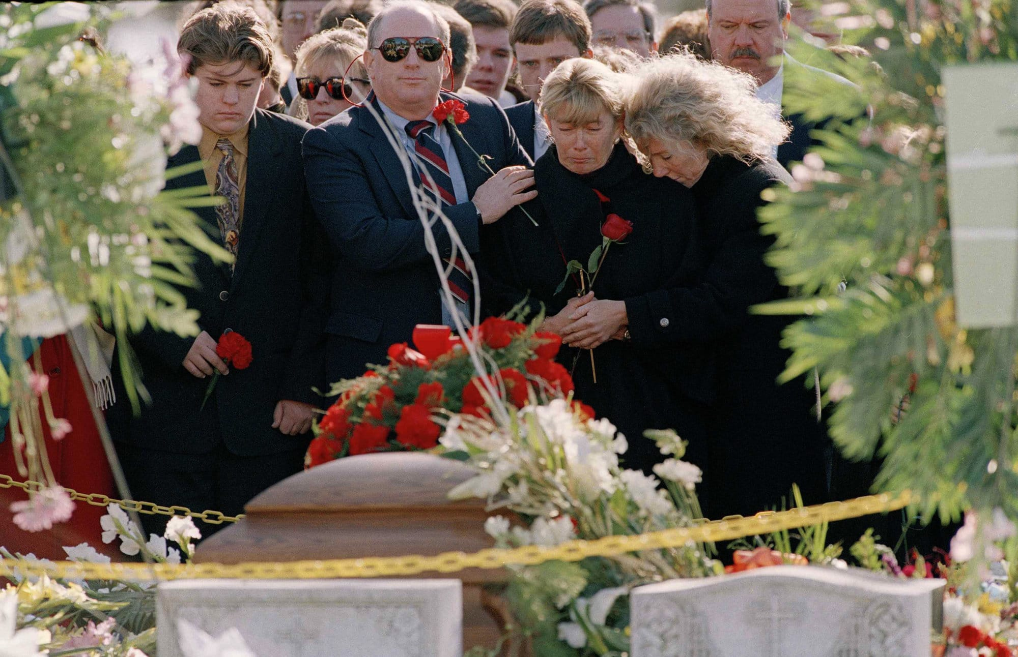 FILE- In this Dec. 13, 1993 file photo, Carolyn McCarthy, center, stands by the casket of her slain husband Dennis McCarthy at Holy Road Cemetery in Westbury, N.Y., Dec. 13, 1993. Mr. McCarthy was shot to death aboard a Long Island Railroad commuter train and their son, Kevin, was critically injured as well. In what was at the time one of the worst mass killings in history, a deranged gunman opened fire aboard a Long Island Rail Road train filled with commuters leaving New York City. Six people died and 19 were injured.  (AP Photo/Mike Albans, File)