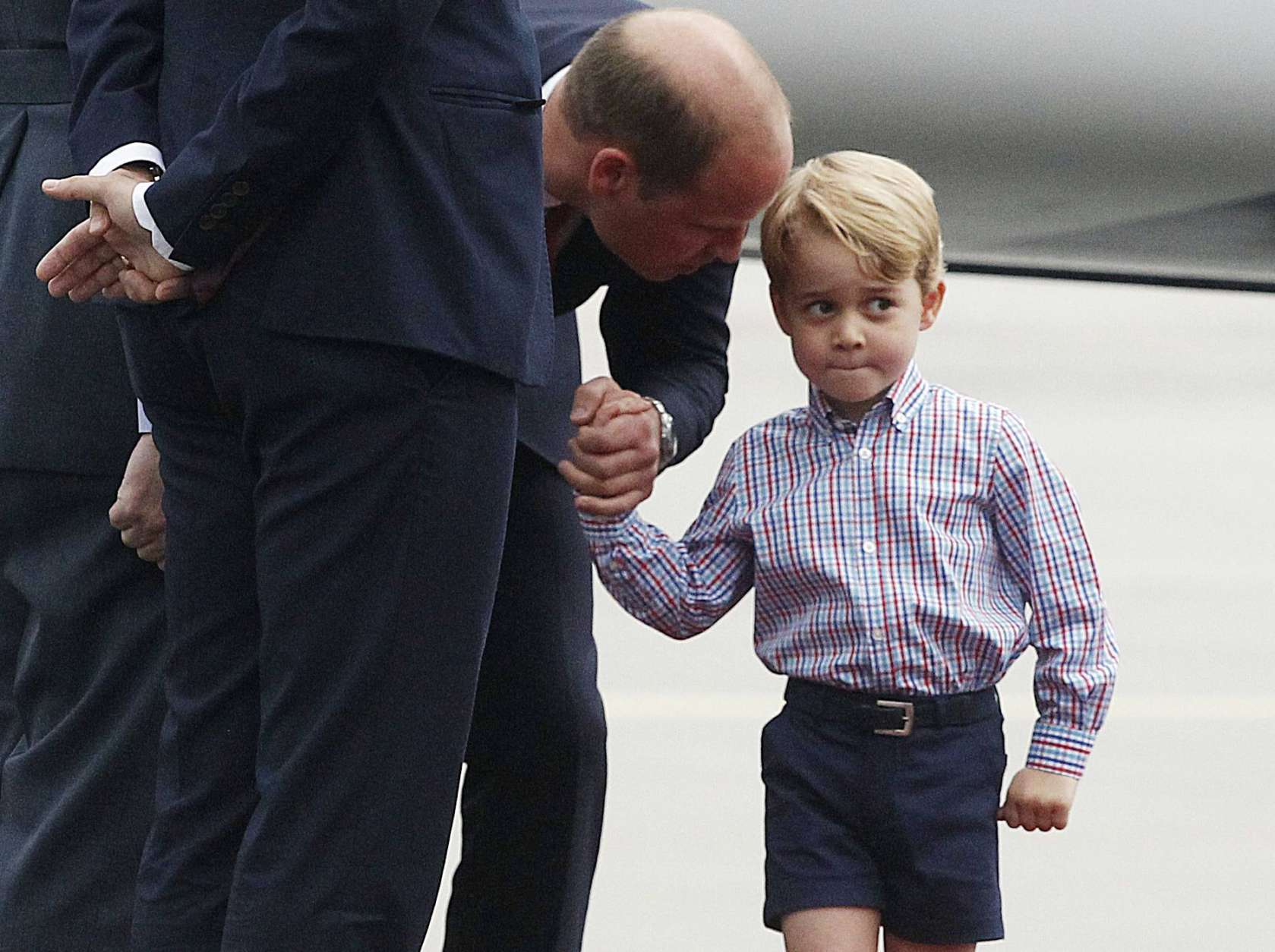 FILE - In this Monday, July 17, 2017 file photo, Britain's Prince William, left, holds the hand of his son Prince George on arrival at the airport, in Warsaw, Poland. A 31-year-old man has been charged in England with sharing a photo of Prince George and details about his pre-school in a social media post prosecutors allege was meant to help others plan terror attacks, it was announced on Wednesday, Dec. 6, 2017. Prosecutors allege Husnain Rashid put the information about the 4-year-old son of Prince William and the former Kate Middleton on the encrypted platform Telegram. Britain's Sun newspaper reports that Rashid allegedly posted the silhouette of an Islamic State fighter beside George. (AP Photo/Czarek Sokolowski, file)