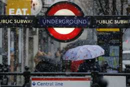 A woman walks away from Notting Hill underground station as snow falls in London Sunday, Dec.10, 2017. (AP Photo/Alastair Grant)
