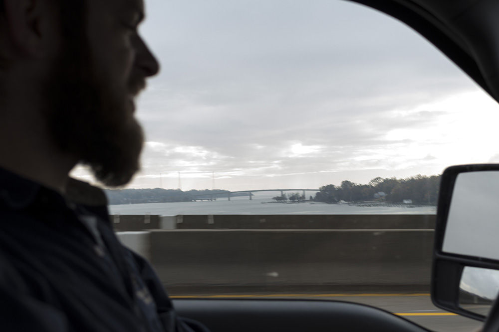 Wayne Witzke from the Shell Recycling Alliance drives the organization's truck Nov. 9 across the Severn River Bridge in Anne Arundel County, Md. Witzke and his colleagues recycle shell to bolster state and federally sponsored, large-scale oyster restoration in Chesapeake Bay tributaries. (Alex Mann/Capital News Service)