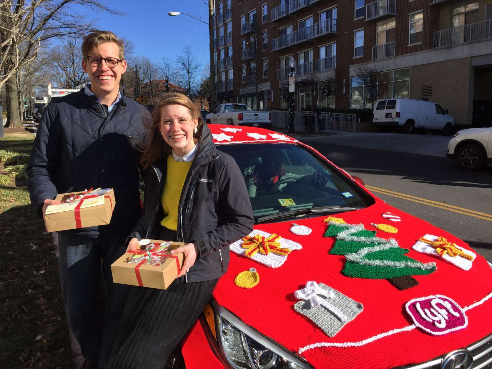 Justin Johansen, of McLean, and Kelly Loggins, of Vienna, happened to be walking by when a Lyft Merry Mode car visited WTOP. They found it highly entertaining.  (WTOP/Kristi King)