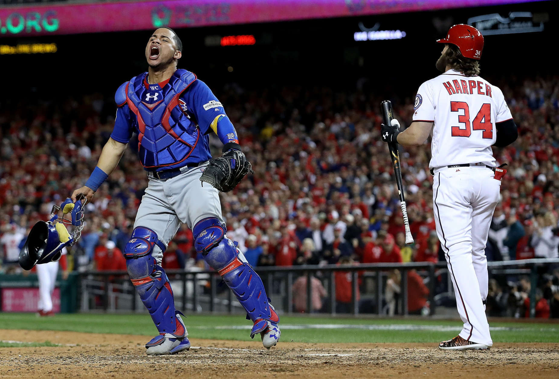 WASHINGTON, DC - OCTOBER 13:  Willson Contreras #40 of the Chicago Cubs celebrates next to Bryce Harper #34 of the Washington Nationals after Harper struck out to end Game 5 of the National League Divisional Series at Nationals Park on October 13, 2017 in Washington, DC. The Cubs won the game 9-8 and will advance to the National League Championship Series against the Los Angeles Dodgers.  (Photo by Win McNamee/Getty Images)