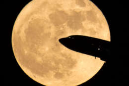 WASHINGTON, DC - DECEMBER 3: In this handout provided by NASA, an aircraft taking off from Ronald Reagan National Airport is seen passing in front of the moon as it rises on December 3, 2017 in Washington, DC.  Today's full Moon is the first of three consecutive supermoons. The two will occur on Jan. 1 and Jan. 31, 2018. A supermoon occurs when the moon's orbit is closest (perigee) to Earth at the same time it is full. (Photo by NASA/Bill Ingalls via Getty Images)