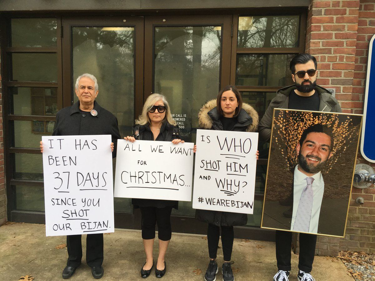 Ghaisar's mom, dad, sister and brother-in-law gathered outside U.S. Park Police District Two Station, just off of the George Washington Parkway Sunday. They held signs and a large, framed photo of Bijan—and were looking for answers. (WTOP/Liz Anderson)