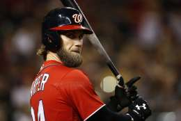 FILE - In this Saturday, July 22, 2017 file photo, Washington Nationals' Bryce Harper waits to bat against the Arizona Diamondbacks during the seventh inning of a baseball game in Phoenix. The Los Angeles Dodgers will pay baseball's highest luxury tax for the fourth straight year and the New York Yankees owe a penalty for a 15th consecutive season. The Dodgers and Yankees vow to get below next year's tax threshold of $197 million. That would reset their base tax rate from 50 percent to 20 percent going into the 2018-19 offseason, when Bryce Harper, Manny Machado and possibly Clayton Kershaw head a potentially illustrious free-agent class. (AP Photo/Ross D. Franklin)
