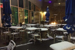 Snow falls on the outdoor dining area of the Grilled Oyster Co. in Northwest D.C. The restaurant's D.C. location is closing but the Maryland one is still open. (WTOP/Patrick Roth)