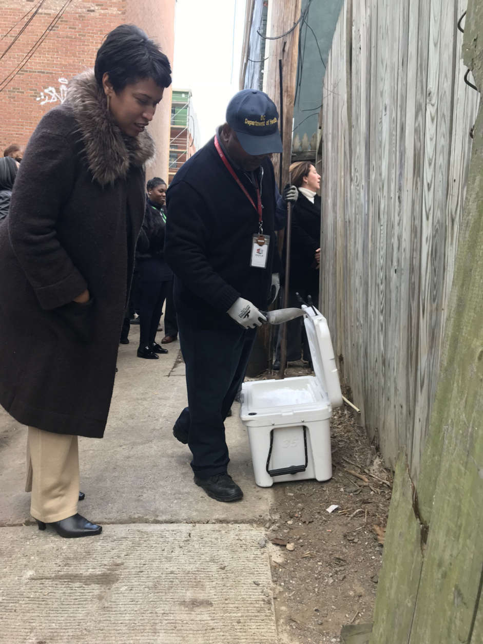 D.C. Mayor Muriel Bowser looks on as a worker with D.C.'s Department of Health puts dry ice in a rat hole. (WTOP/Dick Uliano)
