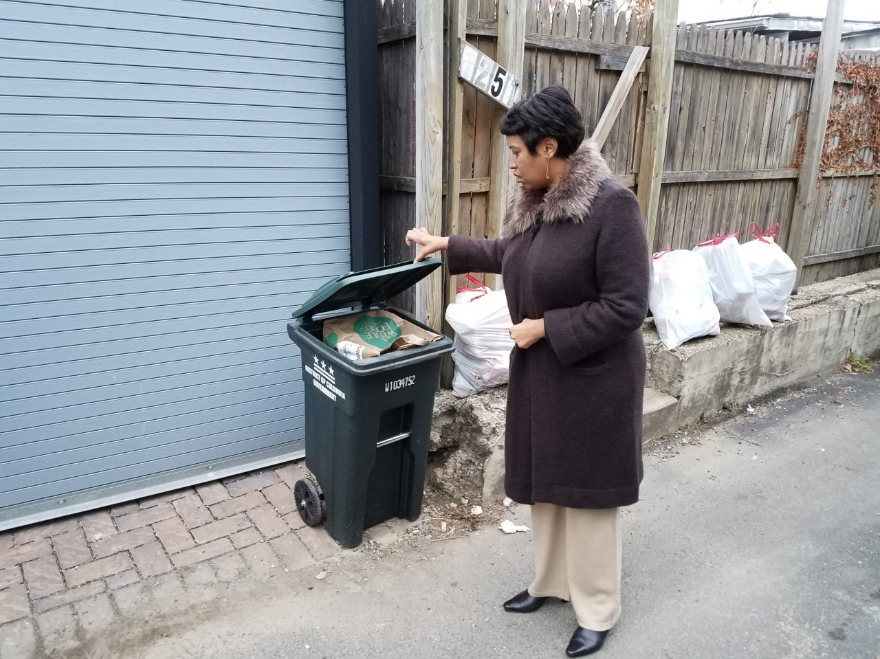 D.C. Mayor Muriel Bowser looks at a trash can in the District. (Courtesy Larry Janezich)