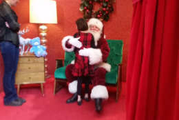Kaylee Lyons gives Santa a hug at inaugural sensory friendly Santa event at Springfield Town Center. Similar events taking place at 375 locations across the U.S. Provides calmer environment, no crowds, no loud noises and no bright lights for children with sensory issues. (WTOP/Kathy Stewart)