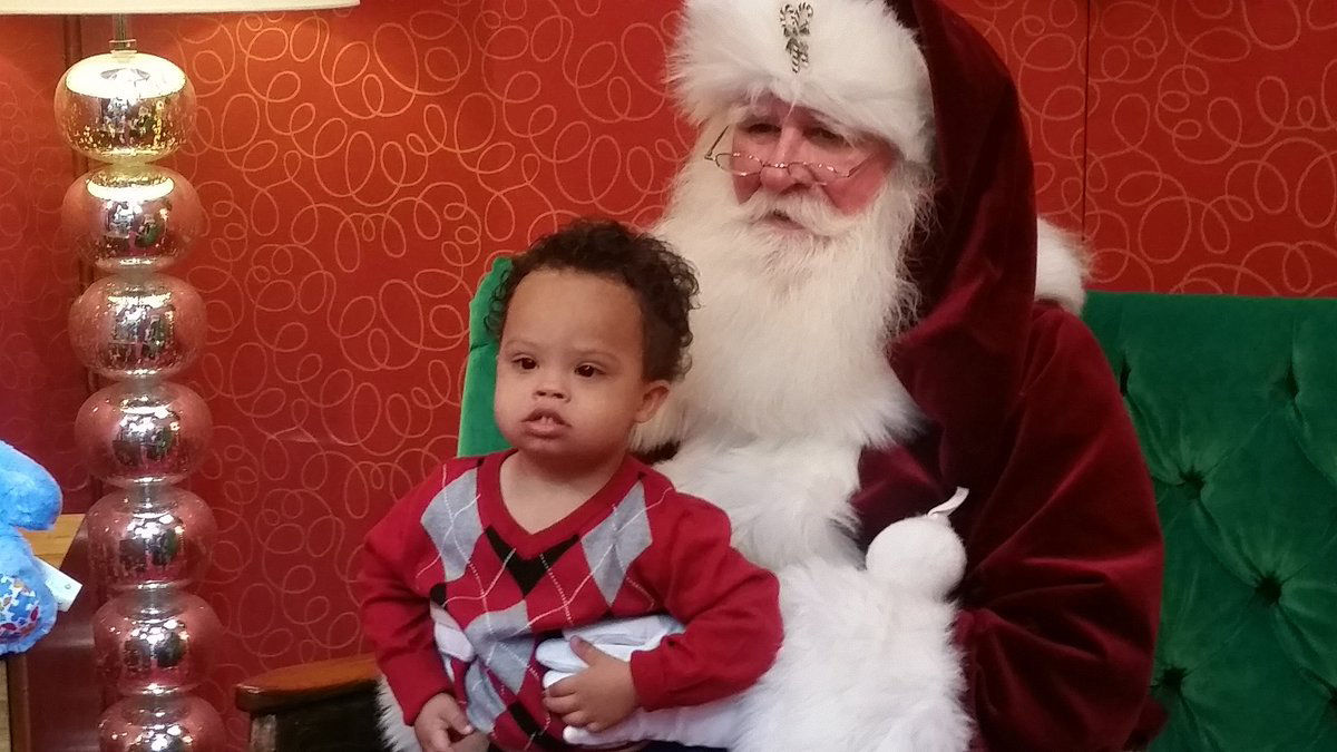 Little Oliver visiting with Santa Claus at the Springfield Town Center during the inaugural sensory friendly Santa event. Children with special needs such as Down syndrome and autism meet with Santa by appointment. (WTOP/Kathy Stewart)