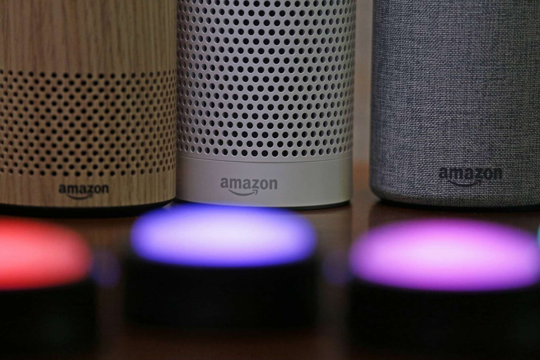 FILE - In this Wednesday, Sept. 27, 2017, file photo, Amazon Echo and Echo Plus devices, behind, sit near illuminated Echo Button devices during an event announcing several new Amazon products by the company, in Seattle. As people get voice-activated speakers and online security cameras for convenience and peace of mind, are they also giving hackers a key to their homes? Many devices from reputable manufacturers have safeguards built in, but safeguards aren't the same as guarantees. (AP Photo/Elaine Thompson, File)