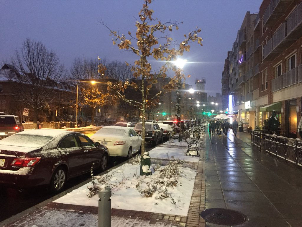 Snow falls on Wisconsin Avenue on Saturday night. A mix of warm temperatures and pretreated roads kept the snow from accumlating on the pavement in most areas. (WTOP/Patrick Roth)