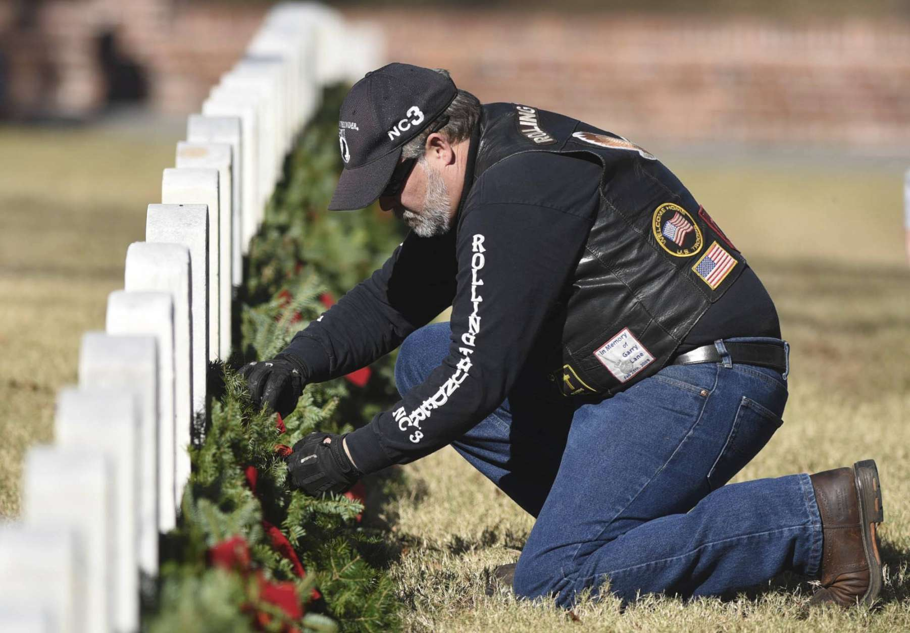 Matt Wall, with Rolling Thunder, places a wreath on a headstone during the annual Wreaths Across America event at Wilmington National Cemetery in Wilmington, N.C. Saturday, Dec.16, 2017. More than 5,000 wreaths were placed on headstones across the cemetery. The program is carried out nationally every December at Arlington National Cemetery, as well as over 1,200 additional locations in all 50 U.S. states, at sea, and abroad.   (Matt Born/The Star-News via AP)