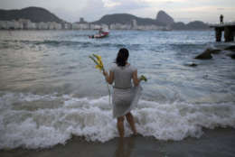 A woman offers flowers to Yemanja, goddess of the sea, for good luck in the coming year during New Year's Eve festivities on Copacabana beach in Rio de Janeiro, Brazil, Saturday, Dec. 31, 2016. The belief in the goddess comes from the African Yoruba religion brought to America by West African slaves. (AP Photo/Leo Correa)